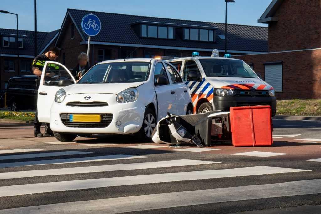 Afslaande auto ziet scooter over het hoofd
