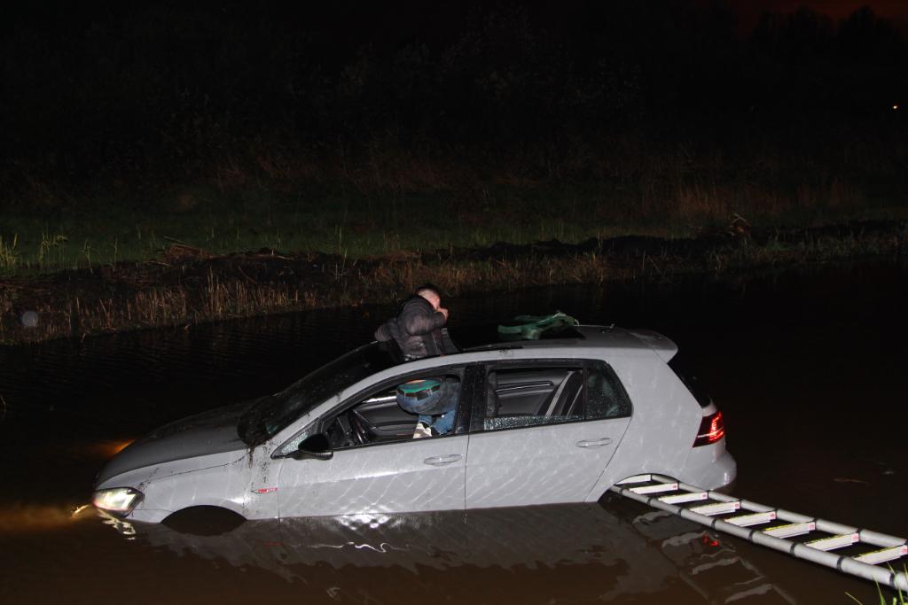 Auto te water op Woudweg