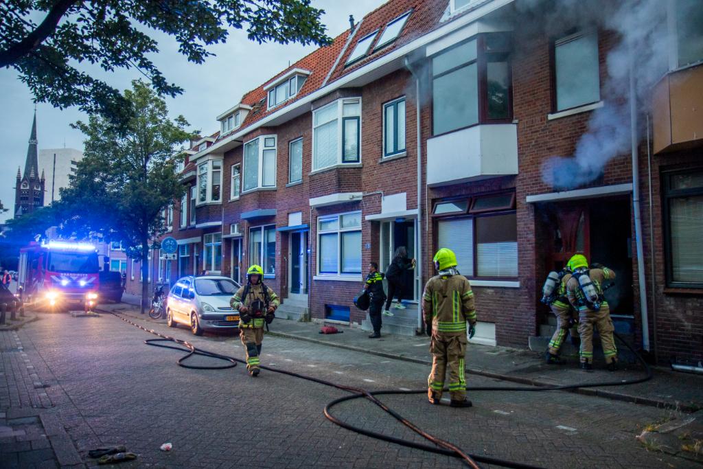 Vlammen achter voordeur te zien