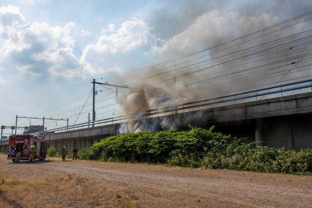 Grote rookwolken bij brand onder spoorwegviaduct