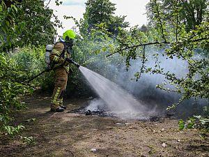 Brandend matras in bosjes bij speeltuin