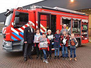 Prijswinnaars Kerstbomenactie op de foto met burgemeester en brandweer