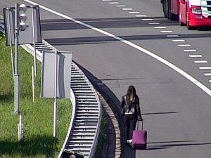 Dame met koffer te voet door de Beneluxtunnel