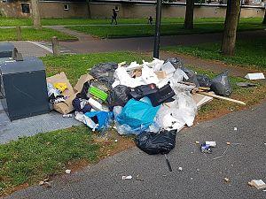 Handhavers doorzoeken zakken vuil om overtreder te traceren