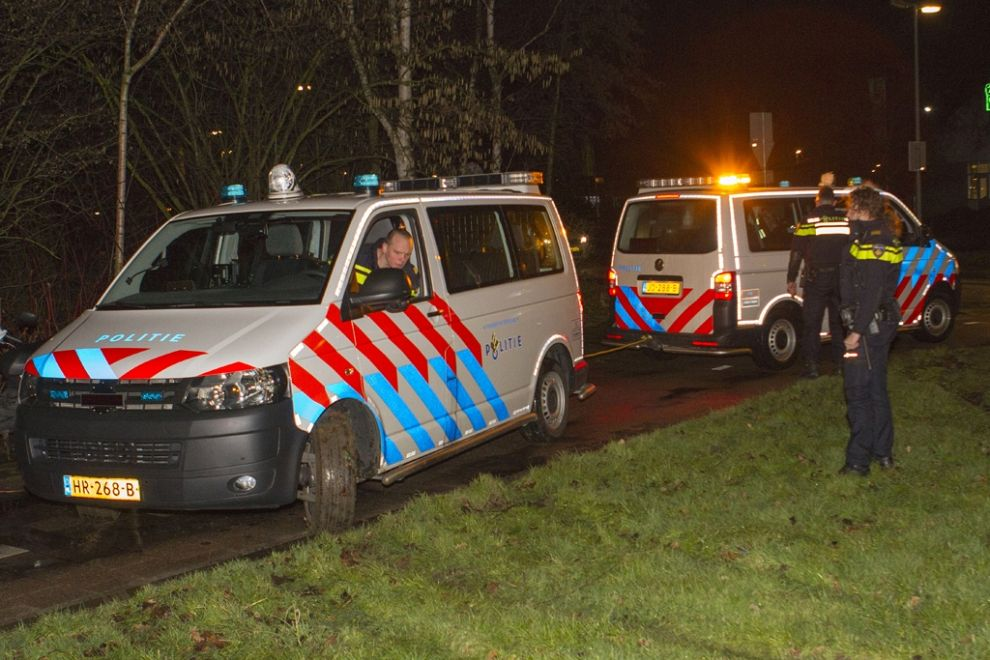 Politiebusje vast in drassig gras